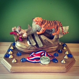 This is the original trophy. Each recipient has taken it upon themselves to add to it. It now includes feathers, a dragon and at least 3 more medals.